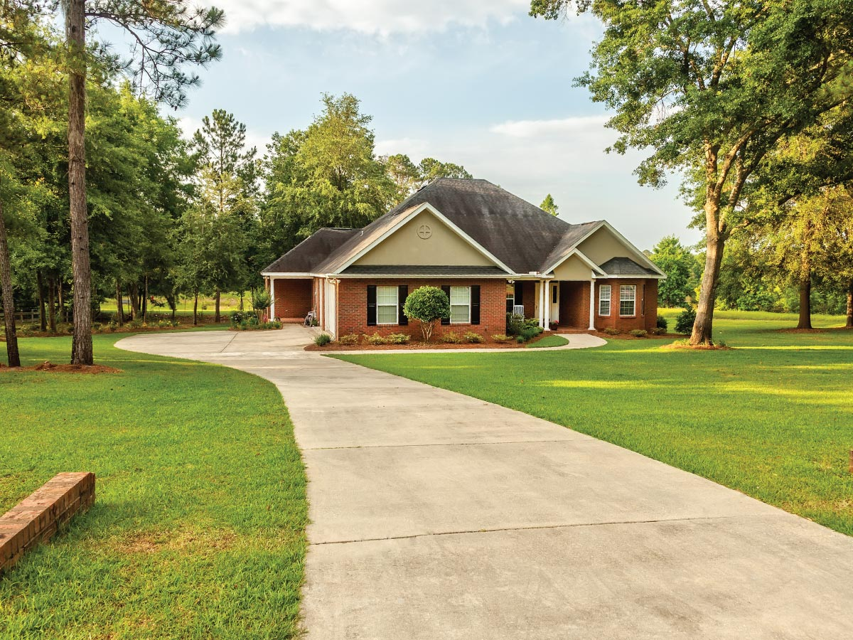 Large house on acreage with long driveway and trees.